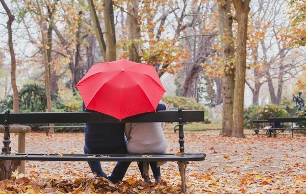 people under red umbrella in the park in fall