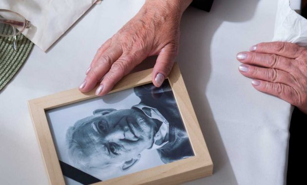 memory visiting training - elderly person looking at old photograph